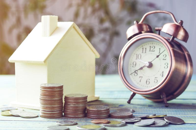 Pile of money, coins growing up with house wood and alarm clock, concept in business about loan, selling,finance, mortgage. And buying home stock photography
