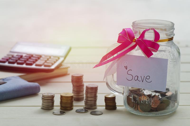 Pile of money coins, with save word on paper and bottle of piggy bank for saving. And business concept royalty free stock image