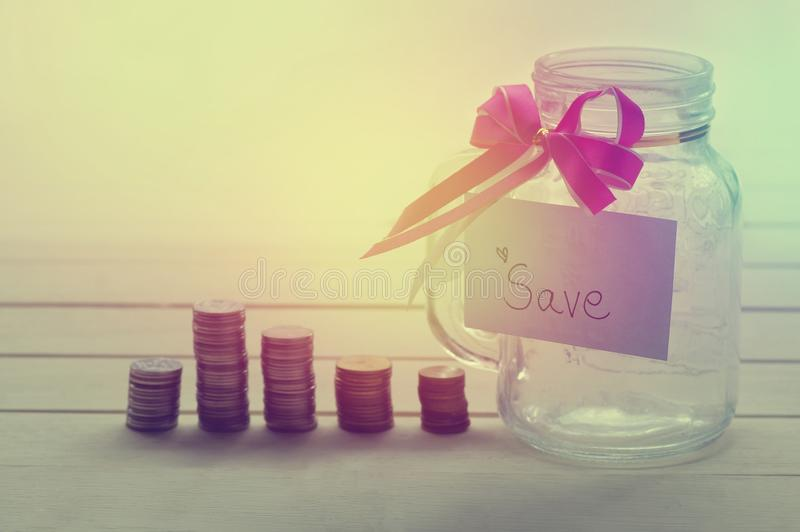 Pile of money coins, with save word on paper and bottle of piggy bank for saving. And business concept stock image