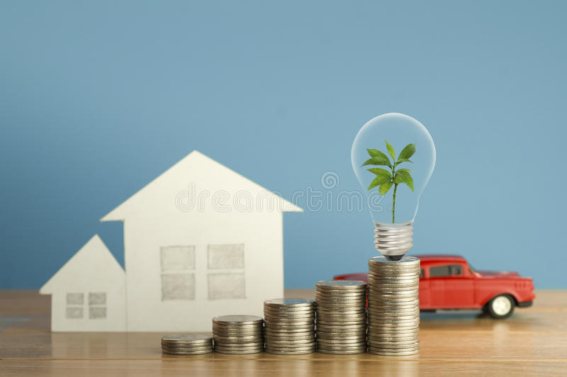 Pile of money coins with small green tree, light bulb, toy car and paper home,on wood and soft blue background, concept royalty free stock image