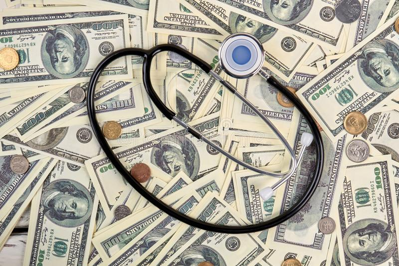 Pile of money and stethoscope. Flat lay, top view stock photo