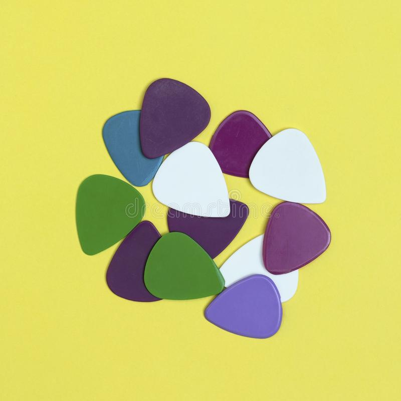 Pile of multicoloured guitar picks isolated on a yellow background. Minimal music concept. Pile of multicoloured guitar picks on a square yellow background stock photos