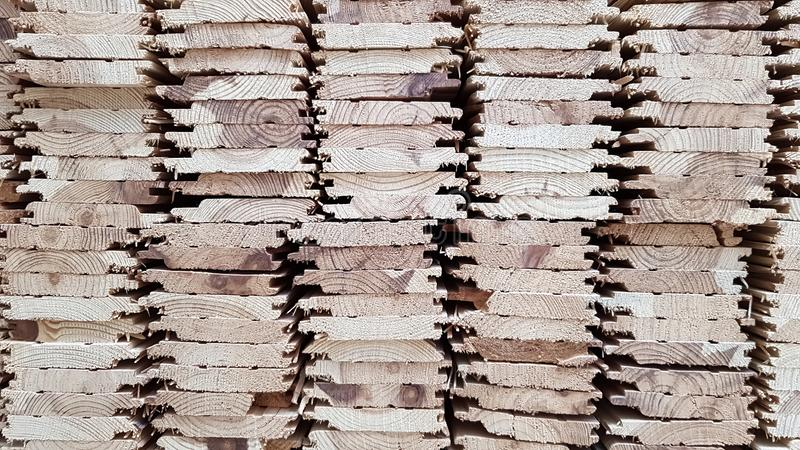 A pile of new wooden boards in stock. Production line of a factory of wooden floors. Industrial background.  royalty free stock photos