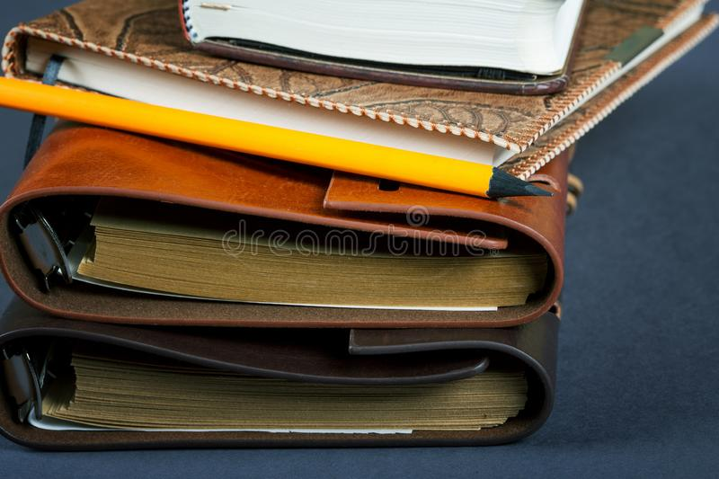 Pile of notebooks in leather covers and a pencil. Close up stock images