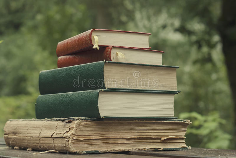 Pile old books. Pile of five old books in a garden wooden table stock images