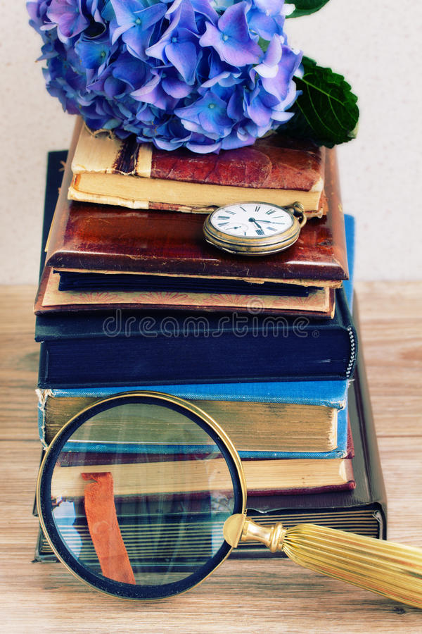 Pile of old books with flowers and clock royalty free stock photos