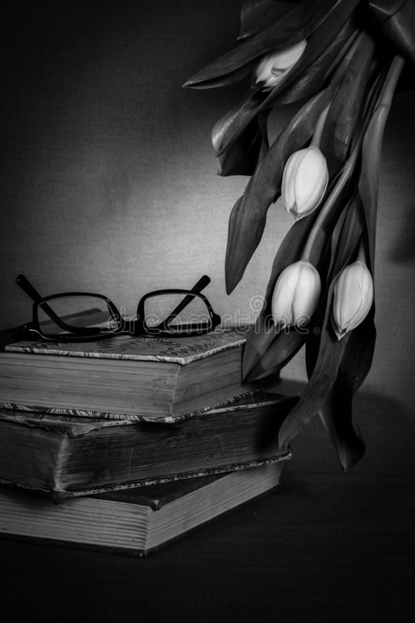 Pile of old books with pair of glasses and white tulips royalty free stock images