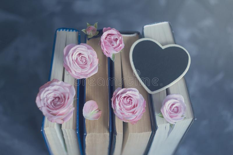 Pile of the old books and pink roses white black chalk board heart on the concrete surface royalty free stock photos