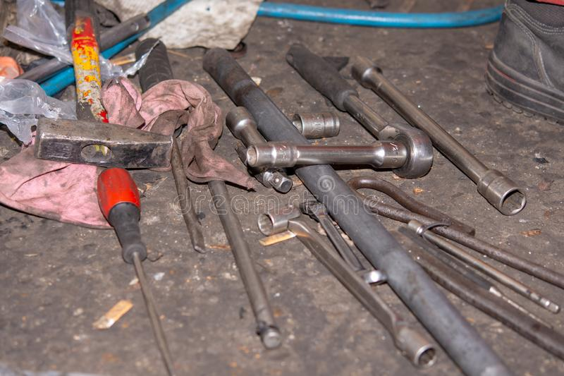 Pile of old and dirty tools in the car mechanic workshop. Screwdrivers and wrench on the floor stock images