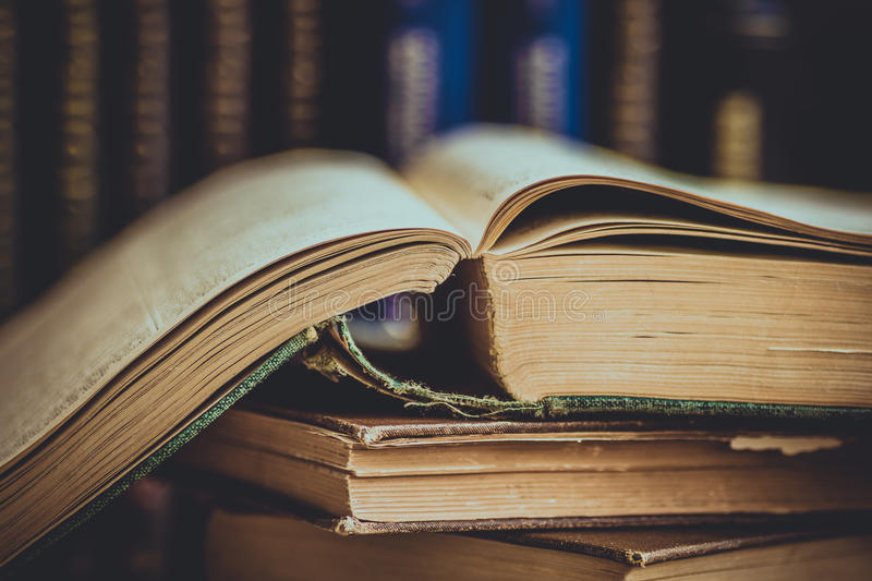 Pile of old opened books, row of volumes in the background, vintage style, education, reading concept, toned stock photography