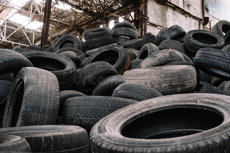 A pile of old rotten rubber tires on the ruined building stock image