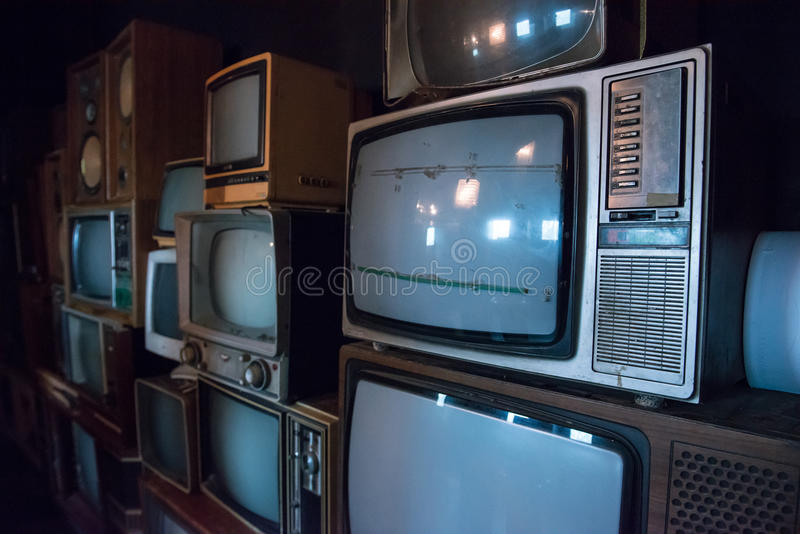 Pile of old televisions. In a dim lit room stock image