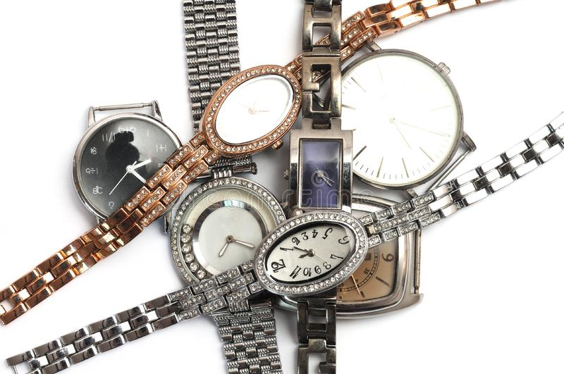 A pile of old unwanted luxury watches in gold and silver. An isolated photo taken on a pile of old unwanted luxury watches against a white backdrop stock image
