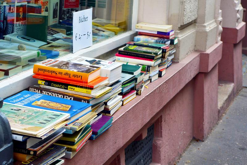 Pile of old used books for sale on windowsill of used goods store stock photo