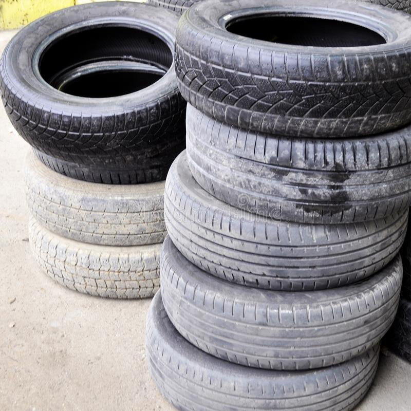 Pile of old used car tires arranged in high piles royalty free stock image