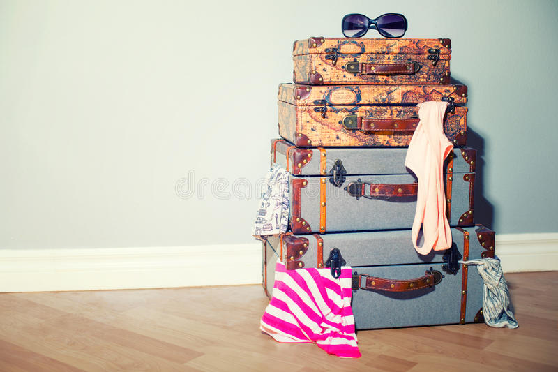 A pile of old vintage travel bags in the room jammed with garments and sunglasses. stock photography