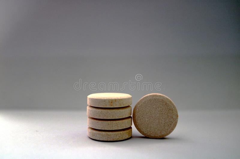 Pile of orange flavored pharmaceutical effervescent tablets with white background royalty free stock photo