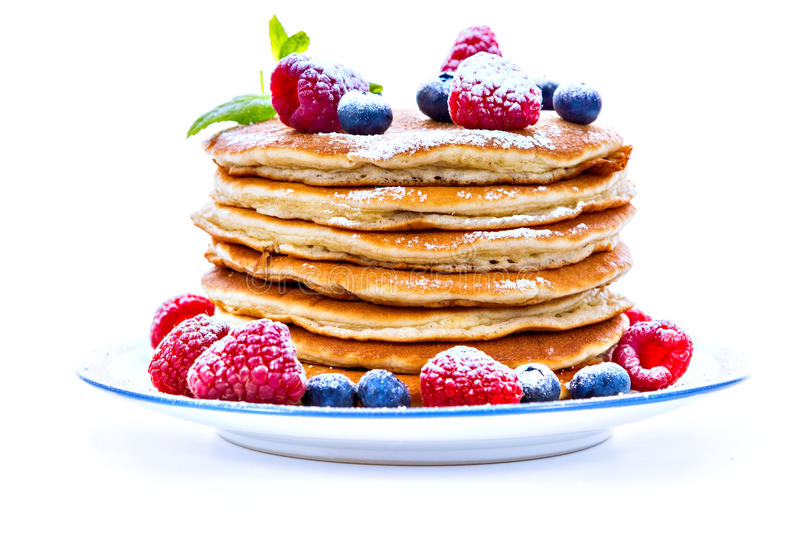 Pile of pancakes with blueberries and raspberries sprinkled with stock photo