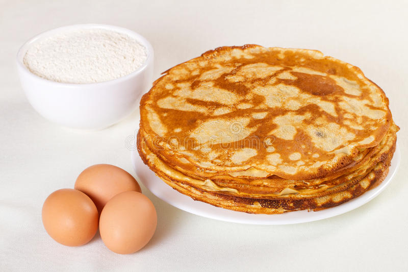 Pile of pancakes with some flour and eggs royalty free stock image