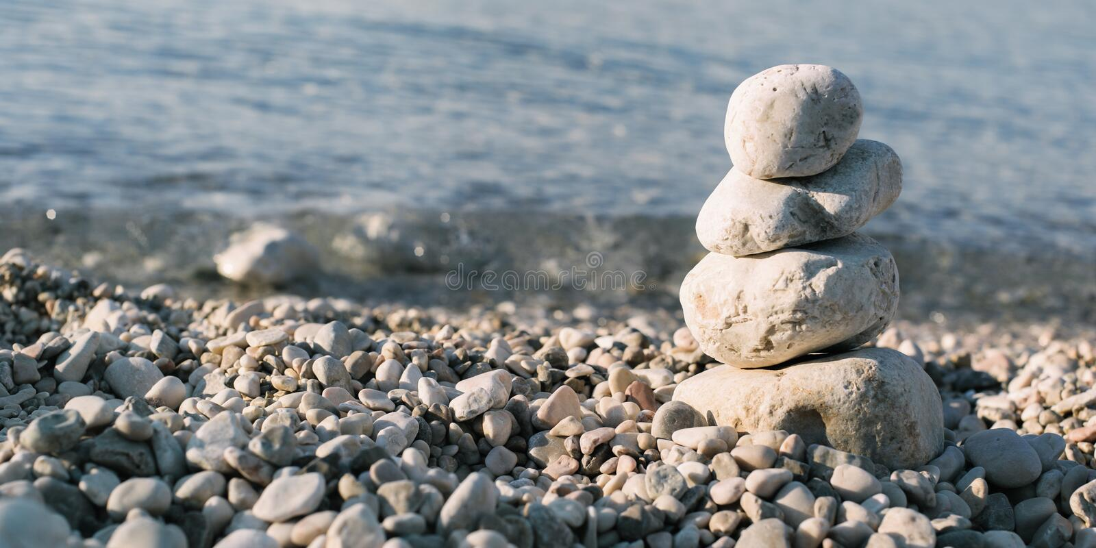 Pile of pebble stones over blue sea in the background royalty free stock images