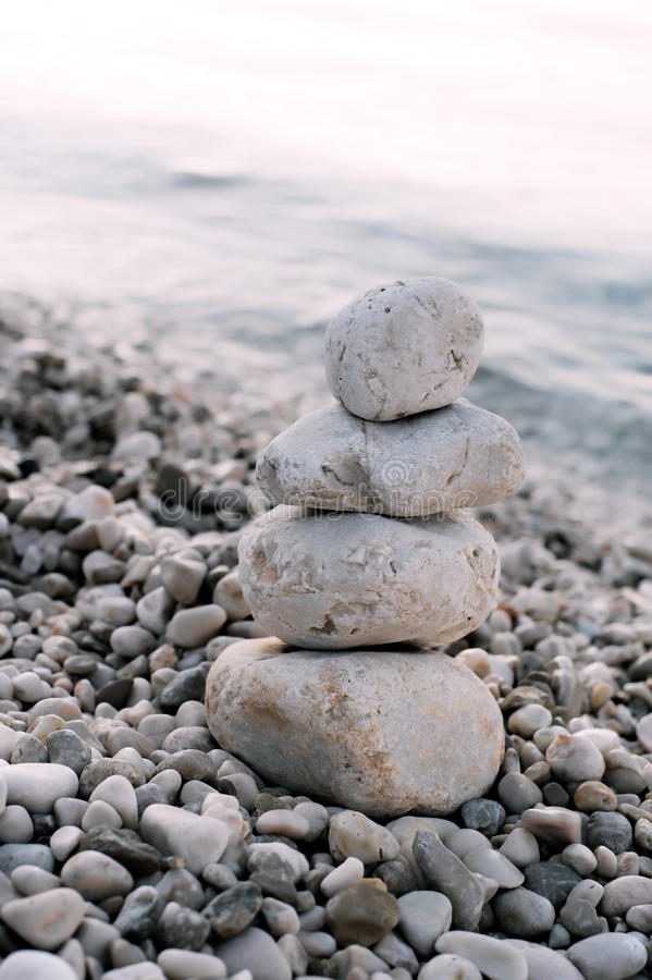 Pile of pebble stones over blue sea in the background royalty free stock photos