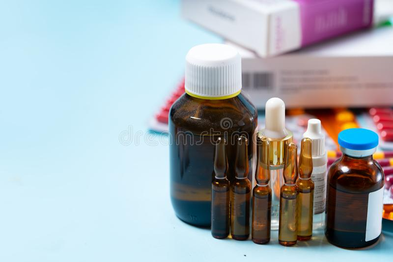 Pile of pills. Pile of colorful medical pills and bottles on blue background with copy space. Drug and antibiotics prescription for treatment medication royalty free stock photo