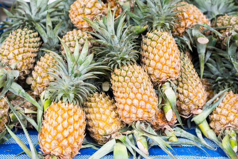 Pile of pineapples at asian market stock photos