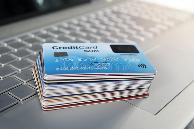 Pile of plastic credit cards on the laptop keyboard. Open access for online shopping using biometric card. Payment cards with. Finger sensor on the surface stock photography