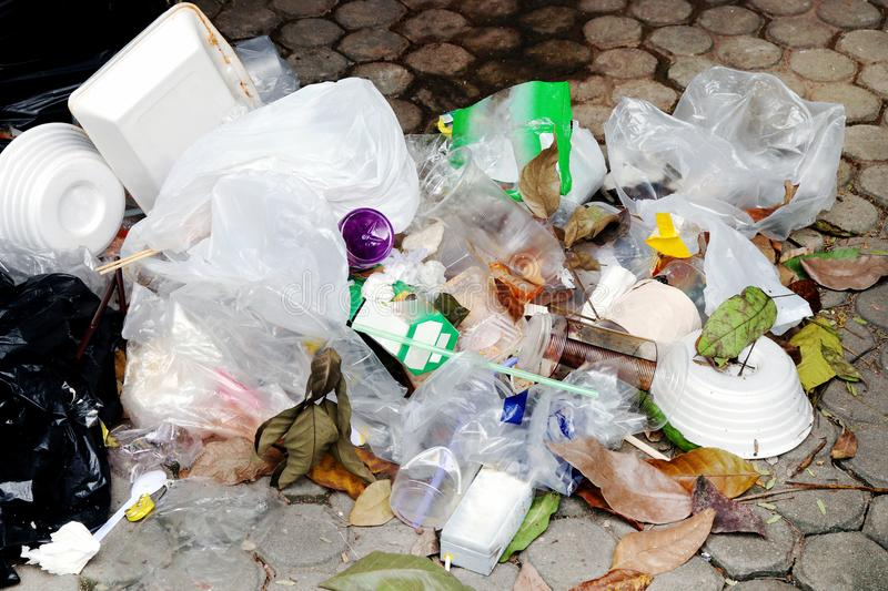 Pile of plastic garbage on the floor, garbage plastic waste glass and straws, plastic bag waste, trash foam tray foods waste royalty free stock photo