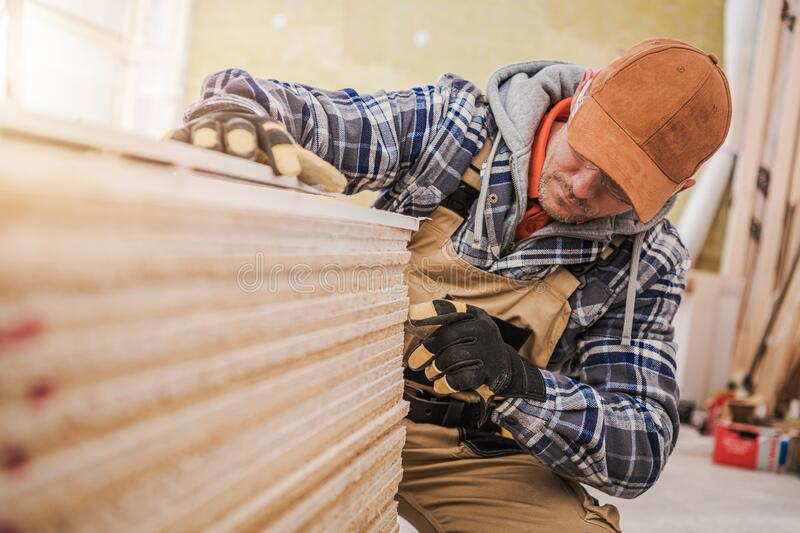 Pile of Plywood Boards. And Caucasian Construction Worker. Industrial Theme royalty free stock photography