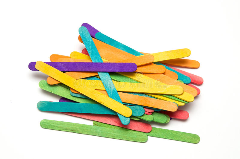Pile of rainbow colored popsicle sticks. A rainbow colored collection of painted popsicle craft sticks over white stock photography