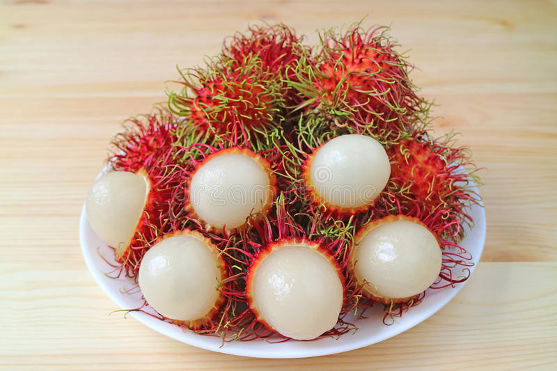Pile of Rambutan Whole Fruits and Opened to Show the Juicy Tasty White Meat stock photo