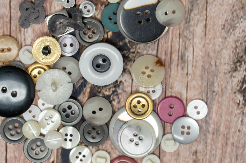 Pile of random colorful shiny sewing buttons isolated on a wood background royalty free stock photo