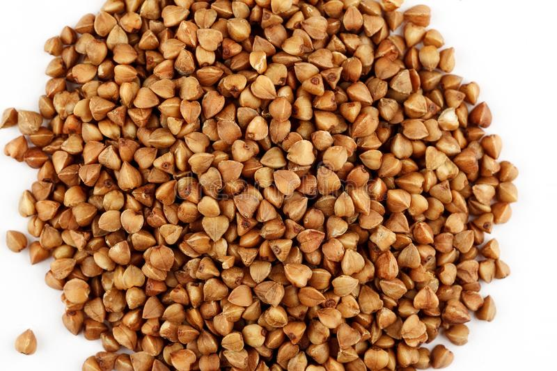 Pile of raw buckwheat seeds on a white background.  royalty free stock photo