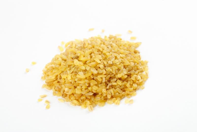 Pile of raw bulgur seeds on a white background.  stock photos