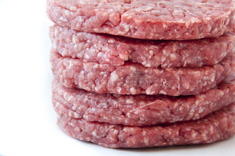 Raw burgers on a white background stock photos