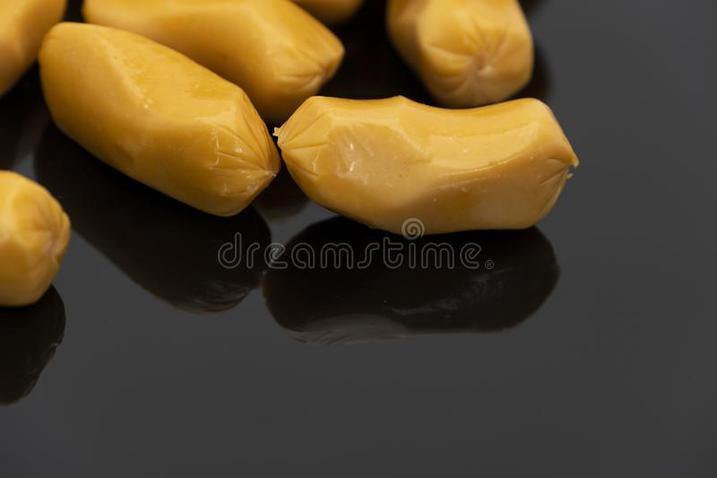 Pile of raw sausages  on black background with copy space text royalty free stock image