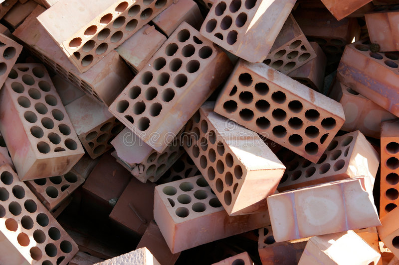 Pile of red bricks with cirlces or holes. Jumbled, messy pile of red bricks with cirlces or holes in them stock image