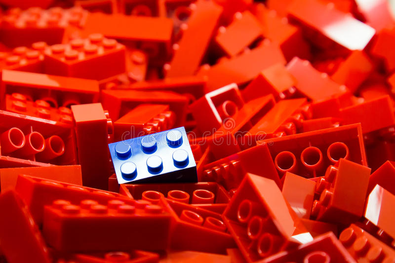 Pile of red color building blocks with selective focus and highlight on one particular blue block using available light.  royalty free stock image