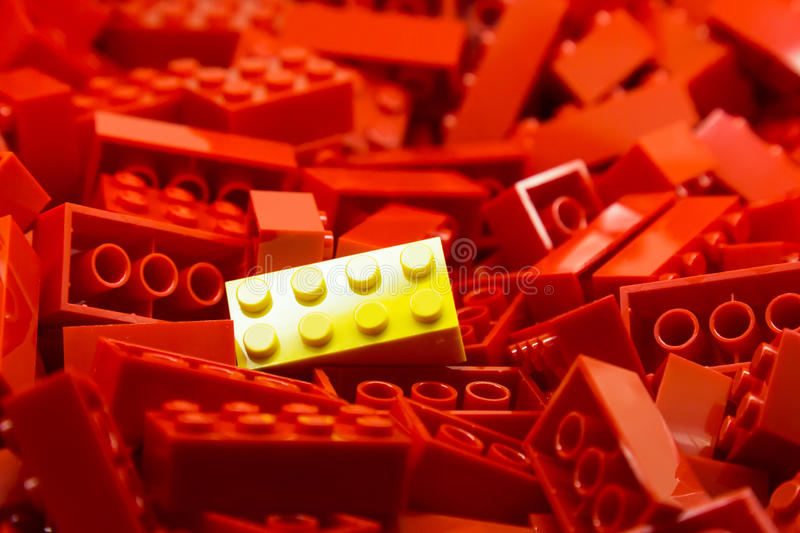 Pile of red color building blocks with selective focus and highlight on one particular yellow block using available light. Pile of blue color building blocks royalty free stock photo