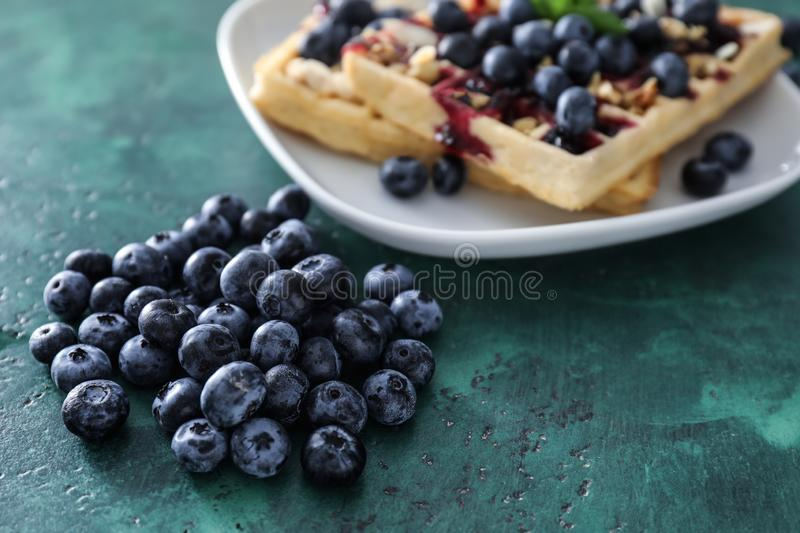 Pile of ripe blueberries with waffles on table royalty free stock image