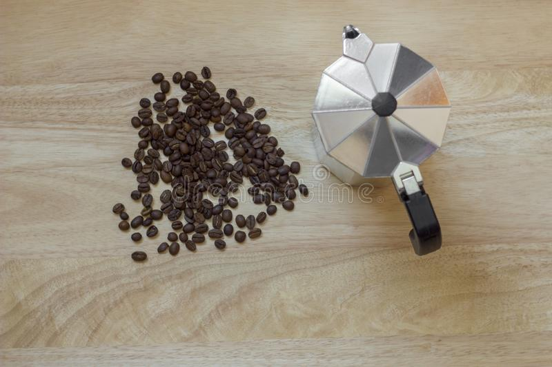 Pile of roasted brown coffee beans on the light wooden surface of the table and a geyser coffee maker, top view stock photo