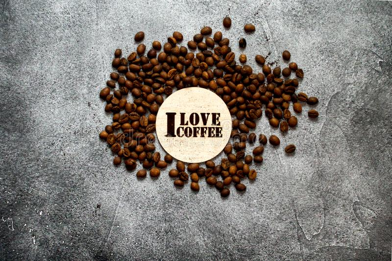 Pile of roasted coffee beans with `I love coffee` wooden stencil. On a rough black background royalty free stock images