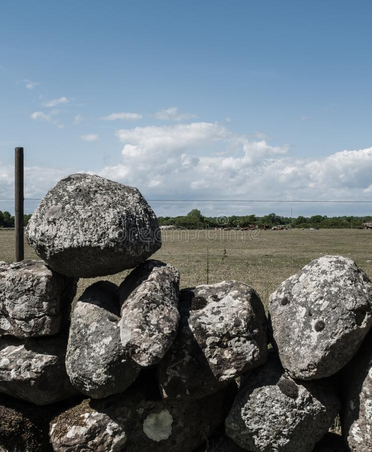 Pile of rocks stacked on top of each other as a fence in a field. A pile of rocks stacked on top of each other as a fence in a field stock photos