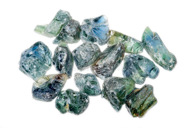 A pile of rough uncut light blue green sapphires stock photography
