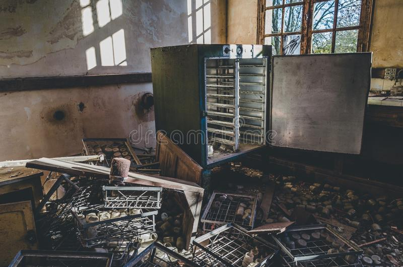 Pile of rusty metal and an opened weathered refrigerator in an abandoned facility royalty free stock photo