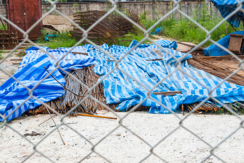 Pile of Rusty Rebars in Construction Site through Metal Mesh Fence.  stock photography