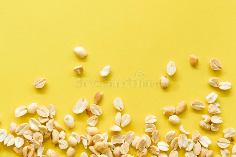 Pile salted and marinated peanuts isolated on a yellow background royalty free stock photos
