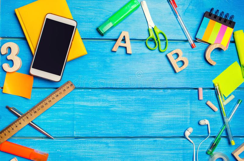 A pile of school supplies on a blue wooden table background. The concept of the educational process, doing homework. Place for text, nobody. Books and royalty free stock photography