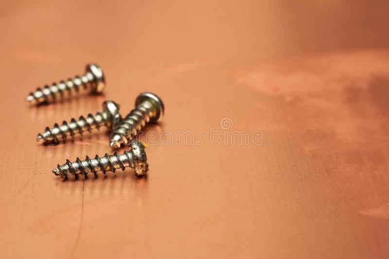 A pile of screws close-up on a background of yellow metal royalty free stock photography
